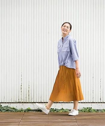 【シャツ×秋色ロングボトムス×スニーカー】 マスタードカラーのプリーツスカートは1枚で秋コーデの主役になるアイテム。秋のそよ風を思わせるような爽やかなコントラストが印象的ですね。