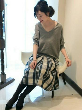 シンプルなグレーのVネックニットと、秋冬らしい素材のチェック柄スカートで女性らしいスタイルに。
