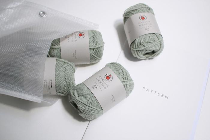 メリノウールで編むフード付きマフラーのキットは、こんな白いバッグに入っています。 このバッグにもちょっとしたお楽しみが。 丈夫で軽いので、毛糸で持ち手を編んで着ければ、かわいい自分だけのエコバッグにもなりますよ♪