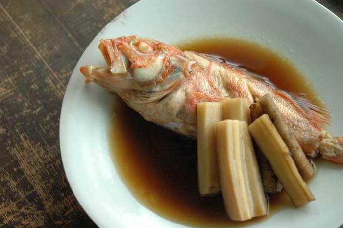 """一見ハードルの高そうな魚の煮付け。切り身の魚よりも旨味がしっかりと出るので、魚好きの方にはおすすめの料理です。フライパンや普通の鍋でも作れますが、圧力鍋で煮ると骨まで食べられるようになるので、魚の骨が苦手な方はお試しくださいね。  魚の下処理で大切なことは、①ウロコをしっかりと取ること、②霜降りをして、臭みのもととなる""""血合い""""や""""ぬめり""""をしっかり取ることです。面倒な場合は、ウロコ取りなどの下処理を行ってくれるお店もありますので、頼んでみても。煮汁は、サゴ、メバル、金目鯛、ブリなど、魚の煮付けの基本となる味付けなので、どんな魚にも応用できます。一緒に合わせる野菜は、長ねぎやごぼう、レンコン、筍、など甘辛く炊いて美味しいものを。  魚を煮付ける際のポイントは、①煮汁が沸いてから魚を鍋に入れること、②魚の煮付けは魚の中に味をしみ込ませずに汁を残して仕上げ、少し濃いめの煮汁に身をつけながら食べることです。魚自体に味を染み込ませようとすると、煮すぎて身が硬くなってしまうこともあるので注意くださいね。"""