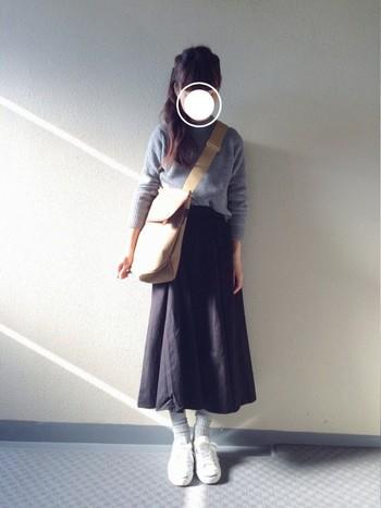 グレーのニットをボリュームのある黒のスカートにウエストインすれば、すっきりメリハリのあるスタイルに。大きめのショルダーバッグは、体を華奢に見せてくれるアイテムでもあります◎