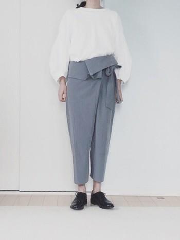 ウエストに大きなリボンのベルトが付いた、ちょっぴり個性的なタイパンツを主役にしたシンプルでおしゃれなコーディネート。こちら無地のも白と黒とグレーの3色だけを使ったスタイルです。エナメル素材の靴はきちんとした印象を与えてくれますね。