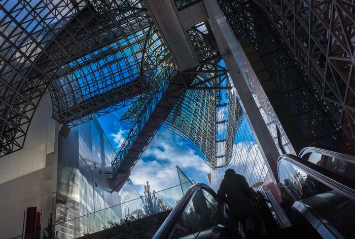 【「室町小路広場」から屋上へと伸びる「大階段(4F~11F)」横のエスカレーター。青空の下に広がるのは「大空広場と葉っぴいてらす」。京都駅ビルは、外界と繋がる広場や歩道が各所に設けられています。】