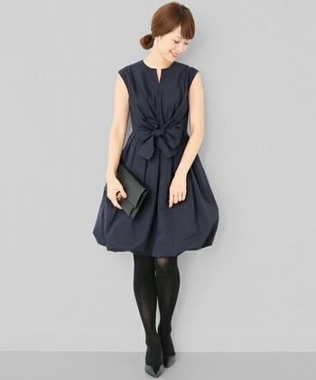 ウエストの大きなリボンが印象的なネイビードレス。裾の絞りは好みのシルエットに調節可能で、黒の小物を合わせて、甘くなりすぎない大人ガーリーなスタイリングになります。