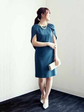 澄んだブルーが美しい、ケープワンピース。ウエストをシェイプした女性らしいシルエットで、肩にマント風に生地を重ねているので、これ一枚でフォーマルシーンもバッチリ。白い小物を合わせてエレガントにまとめています。