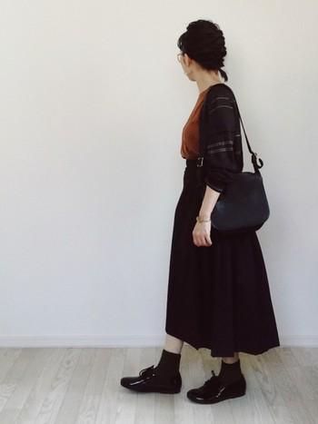黒のスカートにテラコッタのトップスを合わせた旬コーデ。カーキのソックスとエナメルの靴がよくマッチしていて、オシャレ度がアップしています。