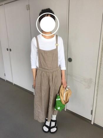 ゆるっと着こなすなら、こんなデザインのサロペットをチョイスしましょう。白とベージュのナチュラルカラーでまとめたコーディネートに、鮮やかなグリーンのバッグを差し色で取り入れるてアクセントに。