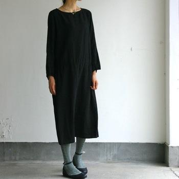 プレーンな印象の無地の黒ワンピース。シンプルながらも着こなしをアップさせるため、グレータイツをセレクトして。少し柄が入ったものを選べば、洗練された印象に。