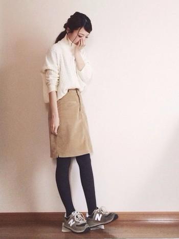 ホワイトのニットに秋の人気アイテムのコーデュロイスカートを合わせた、ミルクティーのようなコーデ。足元は甘くなり過ぎないように、グレータイツとスニーカーでほどよいカジュアルさをプラス。