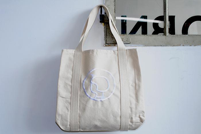 イヤマオリジナルのキャンバストートバッグ。良質のオーガニックコットン100%で作られていて、生成りの生地に真っ白な刺繍が清潔感たっぷりです。大きく刺繍された、おかっぱヘアにリボンをつけたイヤマちゃんがとっても愛らしい。