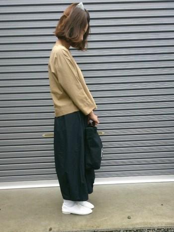 写真は、ベージュのトップスにブラックのバルーンスカート、白のソックスにシューズを合わせた、大人の女性にふさわしい秋のきれいめカジュアルコーディネートです。ベージュ×ホワイト×ブラックの3色コーデも鉄板ですね♪