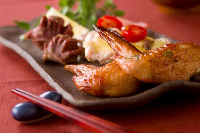 手羽先はオーブンで焼くと、より味わい深くなるですよ♪次は「手羽先のオーブン焼き」のレシピを紹介します。  まず、手羽先は醤油・酒・みりんの合わせ調味料に漬けておいてから、焼き網に油を塗っておいたオーブンで焼き上げます。さらに手羽先だけでなく、鶏ムネ肉や砂肝を加えるとバリエーションが広がりますよ。 そして食べる時には、手羽先の上に七味唐辛子を振りかけると手羽の味が引き立ちます。クレソンとレモンを添えるのも口の中がさっぱりするのでオススメ♪