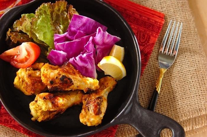 手羽元を使ったタンドリーチキンは、メインのレシピに大人気♪手羽元を袋に入れたら、その中にすりおろしたニンニクとショウガ・塩・カレー粉・ケチャップ・ヨーグルトを合わせて漬けておきます。  そしてフライパンに油を敷き、手羽元を加えて両面に焼き色が付いたら蒸し焼きにします。そして最後の盛り付けの際に紫キャベツ、サニーレタス、トマト、レモンを添えて完成です♪