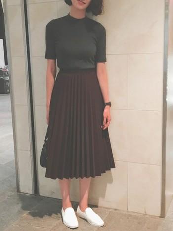 ワインレッドのミモレ丈のプリーツスカートとハイネックリブTを合わせた大人フェミニンなスタイリング。シックな色合いの秋コーデは足元は白のスリッポンで軽さをプラスして。