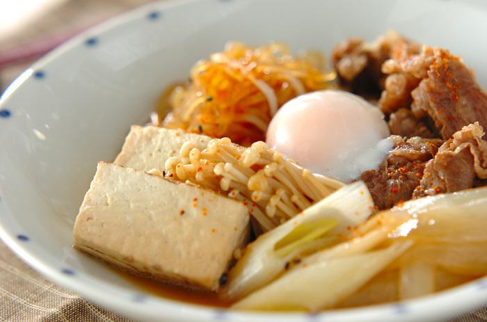 メイン料理にオススメの、すき焼き風肉豆腐レシピのご紹介です。  まず牛肉を炒めて、醤油・砂糖・酒で味付けをしたらネギに玉ねぎ、それにしめじと糸こんにゃくを焼き豆腐と合わせて煮立たせておきましょう。最後に温泉卵を乗せて完成です。お好みで七味をかけて下さいね♪
