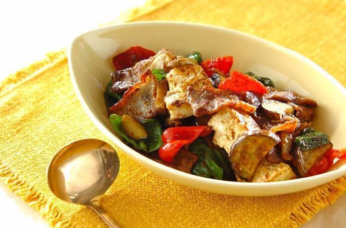 肉豆腐はカレー風味の味付けとも相性がいいんですよ。まずは、下準備で木綿豆腐に塩コショウを振ってから小麦粉をまぶしておきます。 そして豚肉を木綿豆腐、ニンニク、ピーマンに赤ピーマン、ナスと一緒に醤油・ケチャップ・カレー粉・コンソメなどスープの素と一緒に炒め煮をして完成です。ごはんが進むオススメレシピです♪