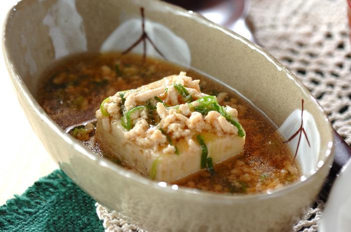 次に準備しておいた挽き肉を先ほどの鍋に入れます。さらに水溶き片栗粉でとろみを付けて刻みネギを加えたら、豆腐を盛り付けた器にかけて完成です。 サッパリとカラダに優しい味ですよ。