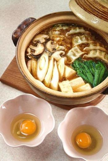 ピリッとした辛さととろみのあるスープが絶品な麻婆鍋は、餃子を入れてボリュームたっぷり。生卵につけて食べると味がまろやかになりますよ♪
