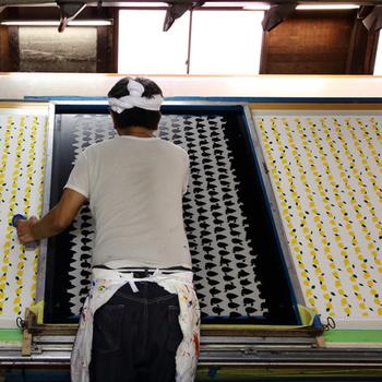 青衣のプリント生地はプリンターなどを使わずに、手捺染という技法で染められています。これは職人さんが一柄一柄、一色ずつ丁寧に染めていくというものです。一色目、二色目とぴったり、色を重ねていきます。職人さんの手で調合された染料の発色も驚くほど美しいですね。