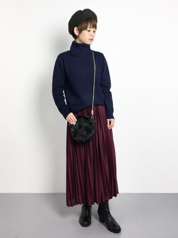 ネイビーのタートルネックにボルドーのプリーツスカートを合わせた女性らしいスタイル。ネイビーとボルドーの組み合わせは上品できちんと感を演出できます。ブラックの小物でさらにシックな印象に。
