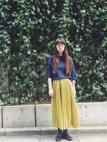 トレンドのプリーツスカートを取り入れたスタイル。ネイビーと明るめマスタードカラーの組み合わせは新鮮でオシャレ。プリーツスカートは重めのコーデをふんわり軽やかにしてくれるからオススメです。
