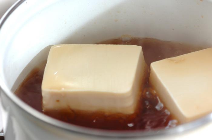 次は鶏挽き肉を使ったサッパリあんかけ肉豆腐の紹介です。 まず、生姜をすりおろしておき、それをギュッと絞ったしょうが汁を鶏挽き肉と合わせておきます。 そして醤油・砂糖・みりんで煮立たせた鍋に豆腐を加えて、しばらくしたら別の器に移しておきます。