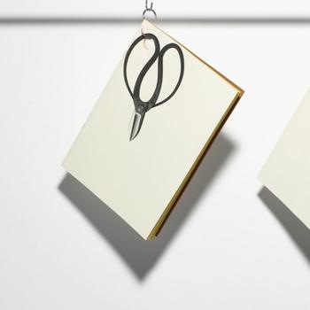ノートの角に穴があいていて、吊るすことができる「ハンギングノート」。まるで、本物のハサミを吊るしているように見える、だまし絵になったデザインです。