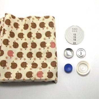 くるみボタングッズの作り方  【材料】 ・ 生地 ・ くるみボタンのキット(押し込んでつくるタイプ) ・ はさみ  【作り方】生地を型紙に合わせて切り取り、くるみボタンにセットします。内側から土台を押し込んだらボタンが出来ます。 あとはヘアゴムをいれたり、ピンを取り付けたら完成です。  ※キットにはヘアゴム向き、ブローチ向きと形状がいくつかあるので用途に合わせてお選びください。