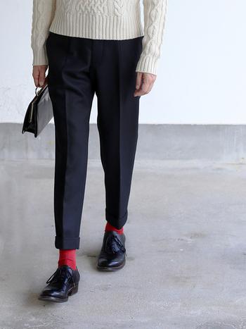 ケーブル編みニットとスラックスを合わせたトラッドスタイルに、赤の靴下を差し色にすることで抜け感が生まれます。
