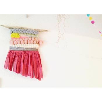 さまざまな太さの毛糸で編まれ、フリンジも斜めにカットされたアートな作品。お子様のいる空間や、大人インテリアのアクセントにしても◎
