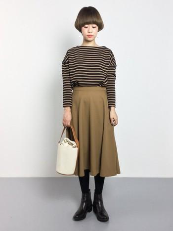 ダークカラーの強い印象のボーダーも、フレアが美しいスカートと合わせて柔らかさを演出。スカートにインするのがポイントです。
