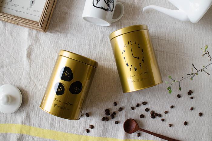 """【コーヒー缶】 札幌出身のアーティスト・サトウアサミさんのイラストが描かれたコーヒー缶。太陽や時計など、""""コーヒーのある時間""""を連想させるモチーフは、食卓にそのまま飾っておきたくなる可愛らしさです。"""