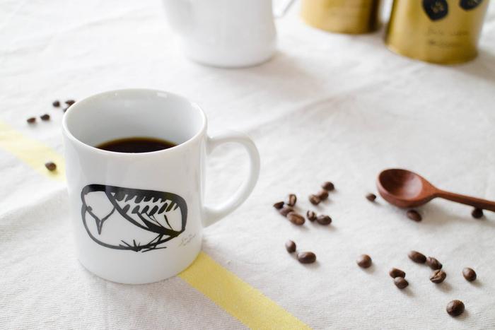 【マグカップ】 佐藤珈琲のカフェでも使用されているマグカップは、コーヒー缶と同じサトウアサミさんのイラスト入り。うつむき加減の鳥がおおらかなタッチで描かれ、ほのぼのとした気分でコーヒータイムを過ごせそう。