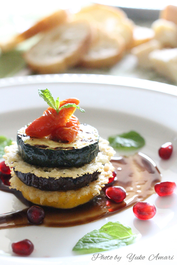 カリッと香ばしく焼いたパルミジャーノをグリルしたズッキーニとナスの間に重ね、アクセントにドライトマトを添えてミルフィーユに。  おもてなしにもピッタリなお洒落な一品です。