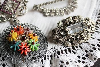 シンプルなお洋服を一気に華やかにしてくれるのが、ブローチです。左側のものは、カラフルなお花がついていて元気な印象。右側のシンプルなものは、なんと約100年前に作られました。大人も楽しめるシンプルな可愛さです。