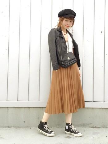 人気のキャメルカラーには、絶対ブラック。女性らしいプリーツスカートに、あえてブラックのライダースとブラックのコンバースを合わせた辛甘MIXスタイル。