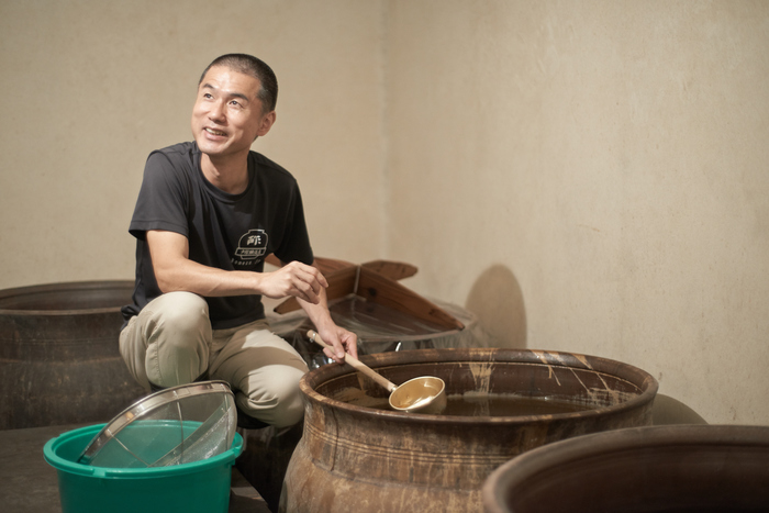 熟成室で出来上がった酢を見せてくれる戸塚さん。甕は背が高いので足場が組まれています