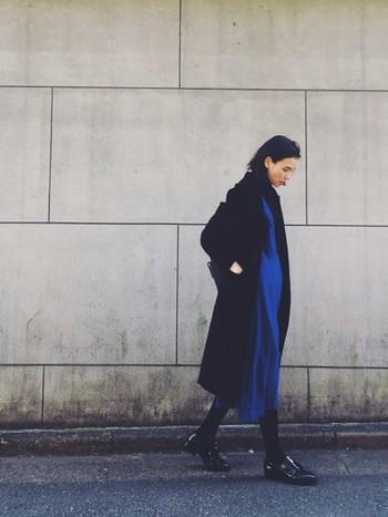 鮮やかなブルーのワンピースに黒のチェスターコートを羽織って、女性らしいワンピーススタイルながらもクールな雰囲気に仕上げたコーディネート。