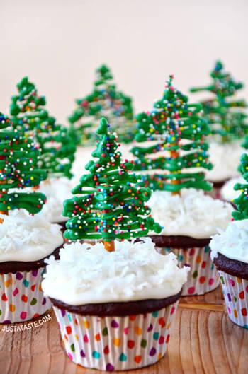 雪の積もったカップケーキの上にプレッツェルとチョコで作ったモミの木をトッピング。  〈作り方はとても簡単♪〉 ①クッキングシートに適当な長さに折ったプレッツェルを並べ、緑色のチョコレートをデコレーションします。その上にさらにアラザンなどをトッピング。 ②ココア味のカップケーキにホイップクリームとココナッツを雪に見立ててデコレーションします。 ③チョコレートが固まったら、クッキングシートから剥がし、カップケーキに刺します。