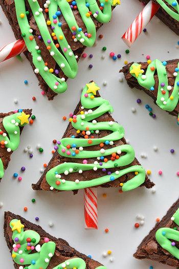 この記事の一番最初に紹介した、ツリースイーツのレシピ。濃厚なブラウニーもクリスマス仕様に変身♪緑色のアイシングカラーやチョコレートはクリスマス時期には手に入りにくくなるかもしれないので、材料の準備だけはお早めに。  〈作り方はとても簡単♪〉 ①正方形のブラウニーを焼く。(市販のものでもOK!) ②三角形にカットし、その上に緑のアイシングやチョコレートで模様をつける。 ③②が乾く前に、アラザンやカラーシュガーでデコレーション、キャンディーバーをさす。※キャンディケーン(スティック形のアメ)の一部を使用。