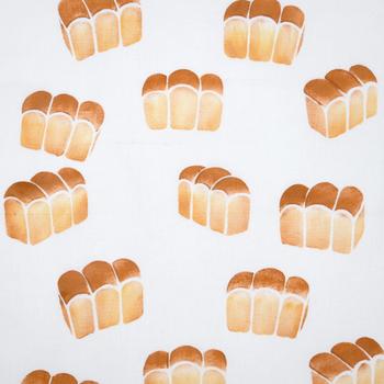 焼きたてのパンがランダムに舞い踊るキュートなデザイン。よく見てみると、それぞれのパンの角度が微妙に異なっていて、染め型が違うことがわかります。