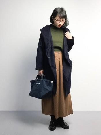 カーキのタートルネックにベージュのロングスカート。さらにネイビーのコートを羽織って、全体をアースカラーでまとめたコーディネート。寒い季節にそっと寄り添う、落ち着いた雰囲気に。毎日着るコートは、ネイビーのような万能カラーを選ぶのが正解です。