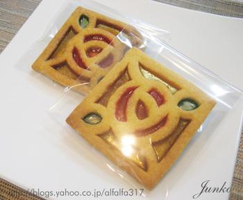 クッキー生地に型紙を当てて切り、さまざまの色の飴をはめ込んで焼いているようです。素敵なアクセサリーのようですね。