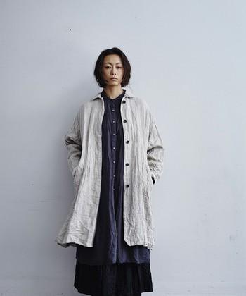 シワ感のある風合いで、装いをナチュラルな雰囲気にしてくれるステンカラーコート。後ろ見頃に入ったたっぷりのギャザーと黒いボタンで、アンティークな雰囲気も感じられるコートとなっています。
