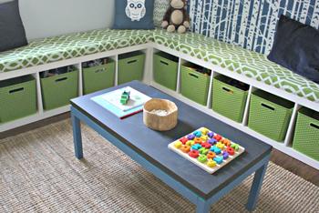 プレイテーブルをぐるっと囲むような形でL字型の収納が配置されています。収納棚の上にはクッションマットが敷いてあり、ベンチがわりに座って絵本を読んだりすることもできます。