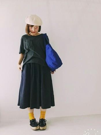 ブラックコーデに挿し色で、ブルーのトートバッグやイエローの靴下などを合わせてアクセントを。