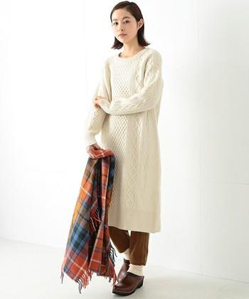 ほっこりとしたケーブル編みが魅力のニットワンピースはシンプルで飽きのこないデザインです。パンツとサボのバランスが◎シンプルなコーディネートには、チェック柄のストールをアクセントに添えて♪