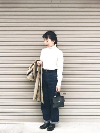 シンプルな白のタートルネックニットにゆったりシルエットのデニム、ドレスシューズ、レザーのハンドバッグ、ステンカラーコートを合わせて。シンプルだけどひとつひとつのアイテムにこだわりが感じられる、清潔感のある素敵なコーディネートですね。
