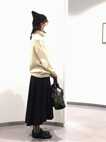 エルボーパッチがポイントのホワイト系のざっくりタートルネックニットに、後ろに流れるようなシルエットが魅力なスカートを合わせたナチュラルなデザインコーディネート。モノトーンコーディネートのアクセントとして、タイツやバッグに柄を持ってきてあなたらしさをプラスして♪