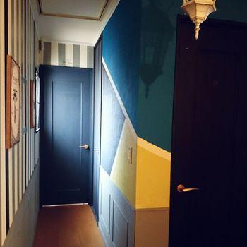 「AFTER」完成したのは、ギャラリーかカフェのような、3色使いのスタイリッシュな壁。廊下の対面はストライプ柄に額を飾り、正面には玄関ドア…さまざまな色・柄の要素が混じり合っているのに爽さかにすら見えるのは、絶妙な配色センスの賜物。
